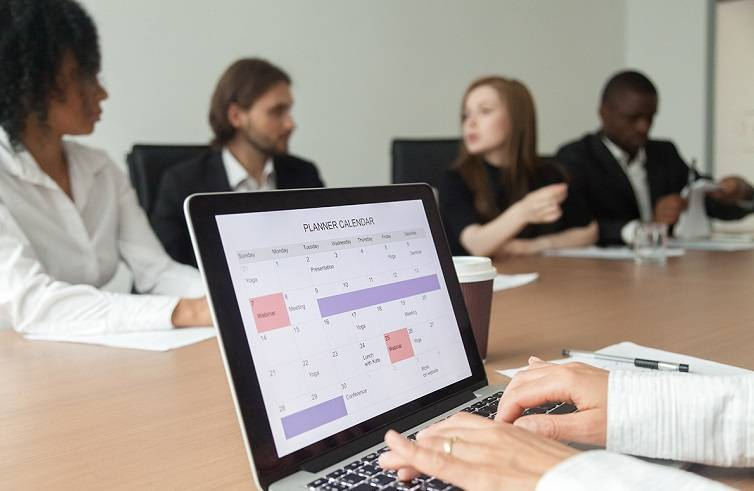 Woman planning work or making events schedule with planner calendar